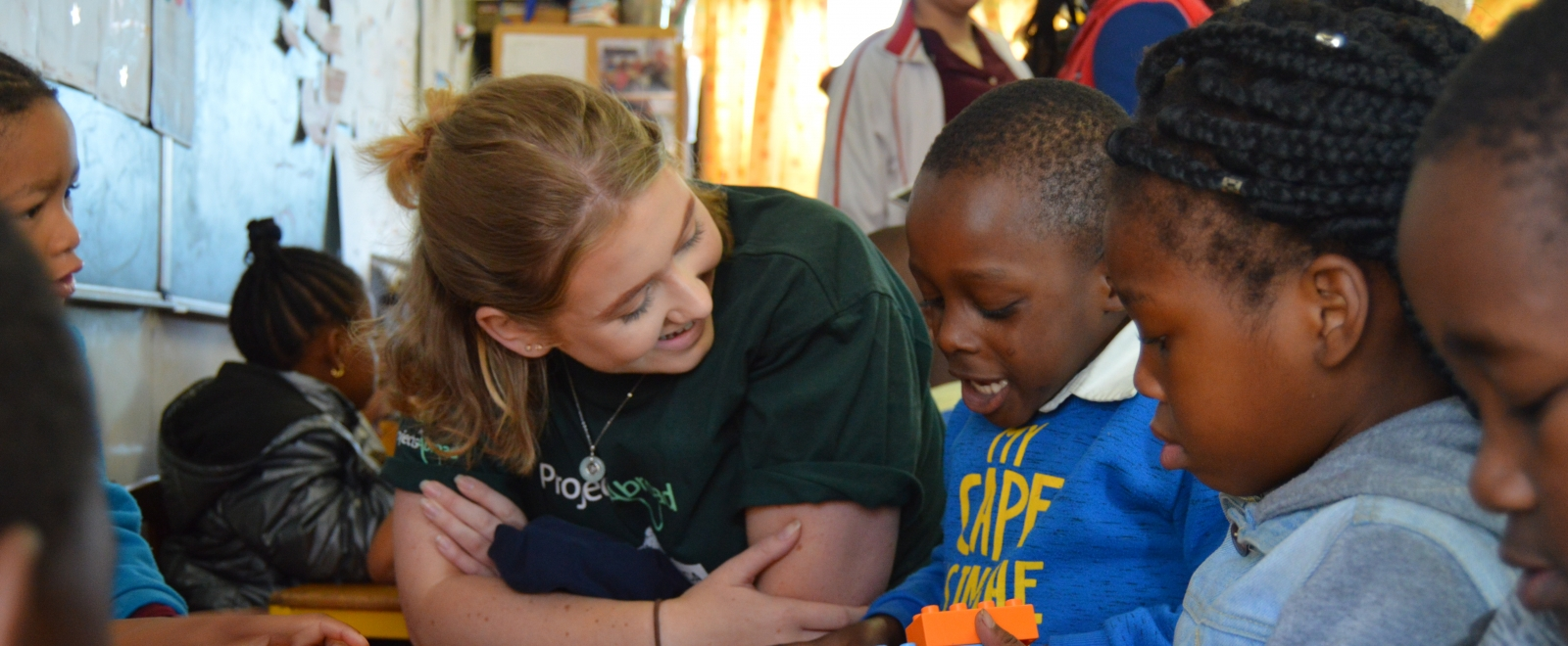 A volunteer works with young children on a high school summer travel program abroad